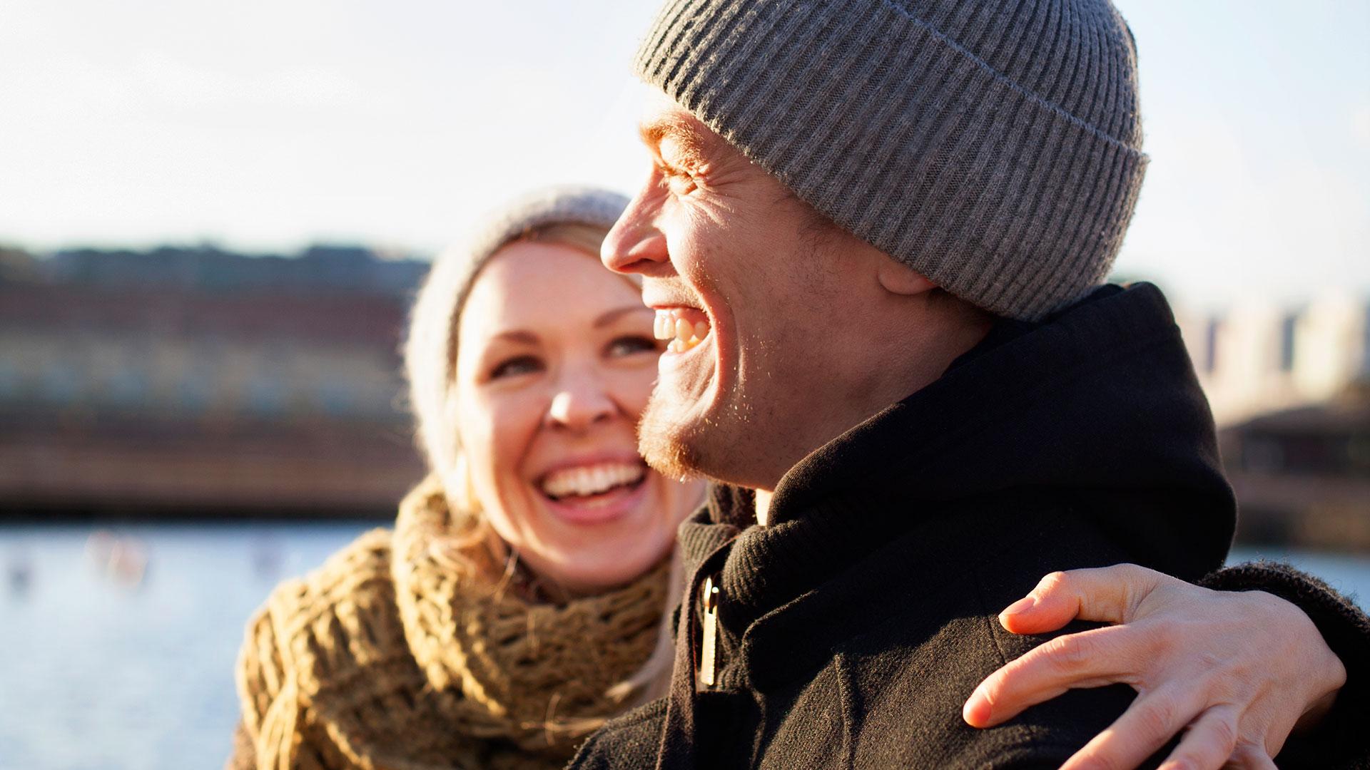 Hymyilevät nainen ja mies auringonpaisteessa.