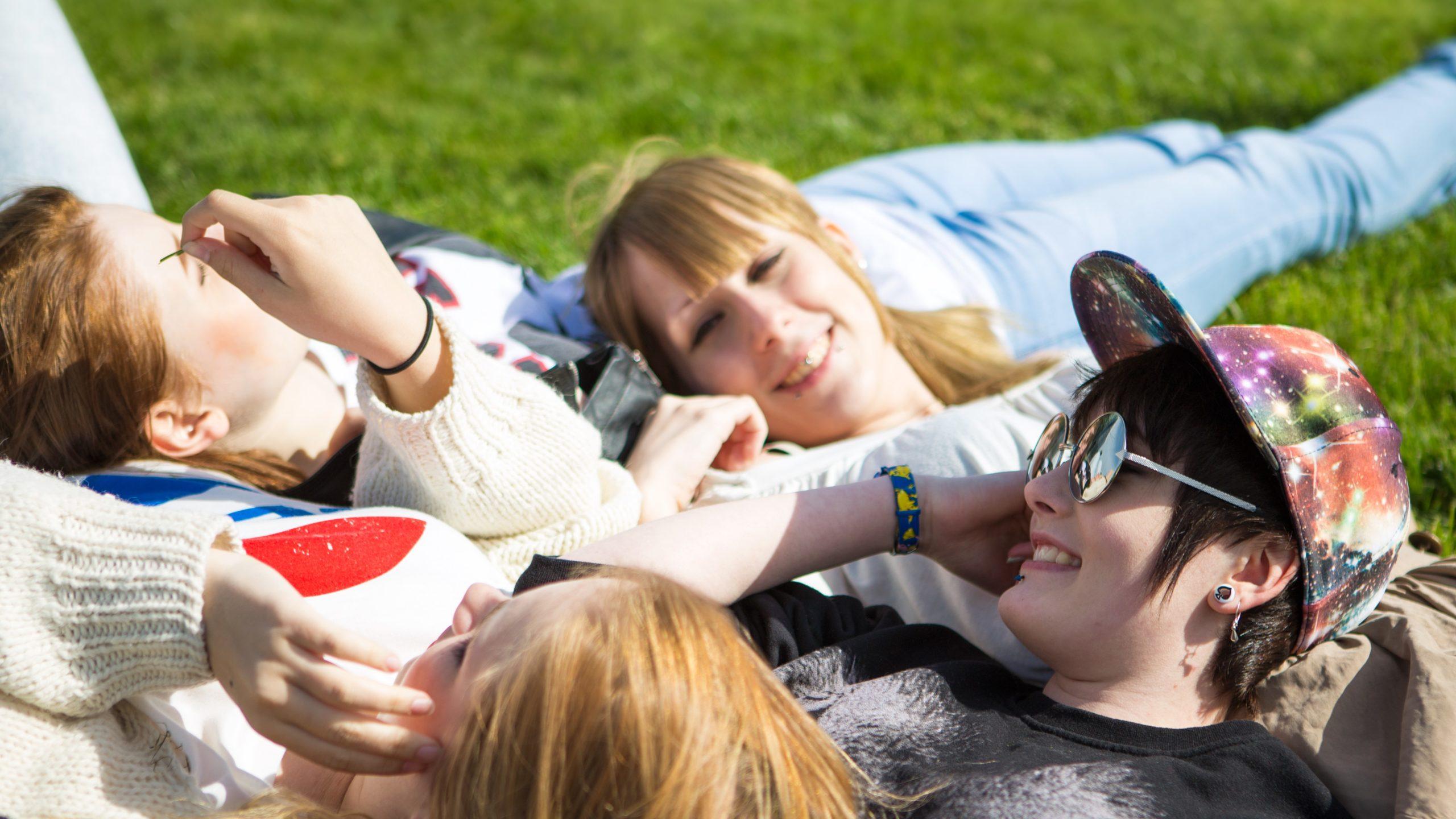 Joukko nuoria makoilevat lähekkäin nurmikolla auringonpaisteessa.