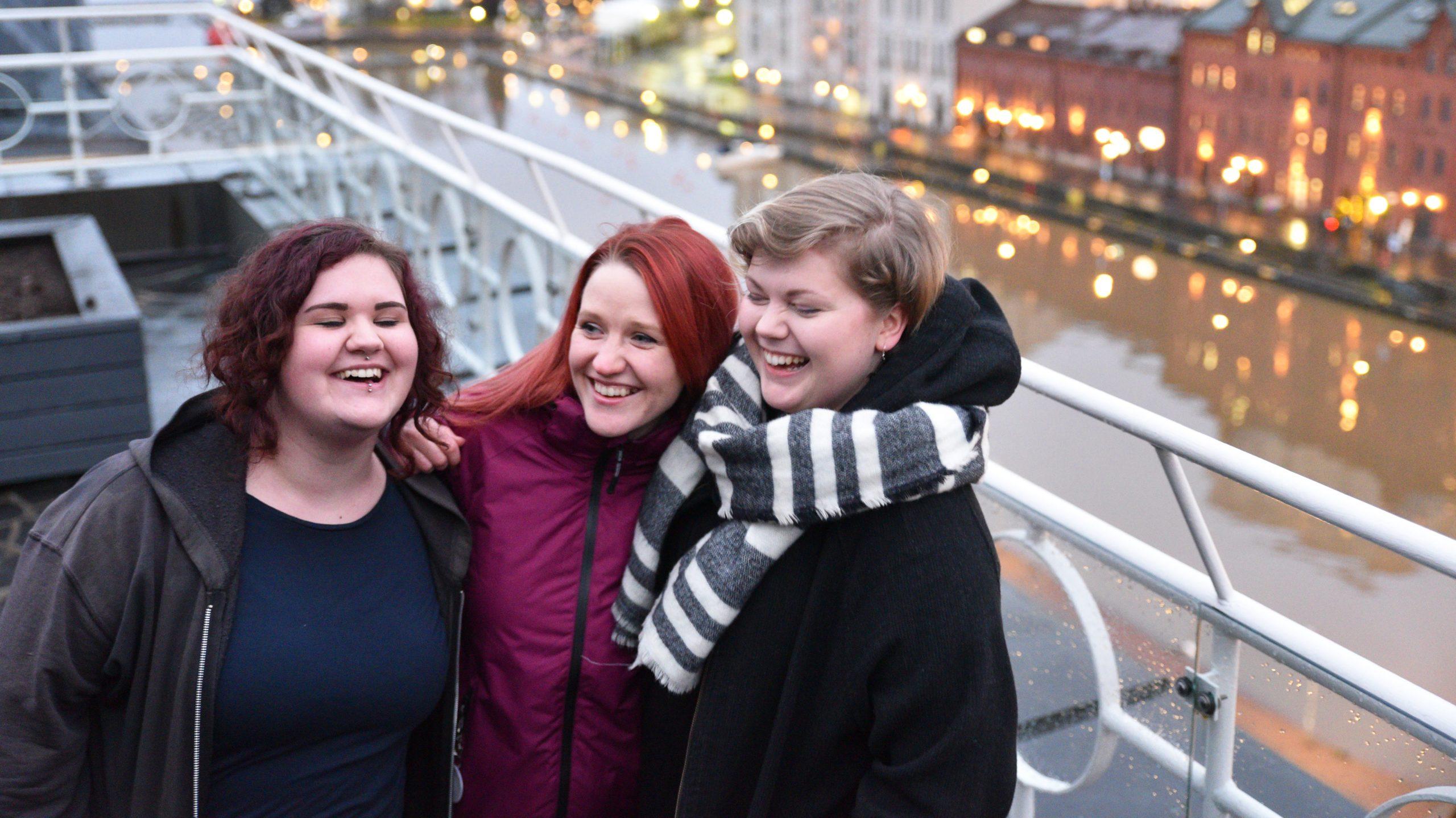 Kolme naista seisovat hymyillen parvekkeella ja taustalla näkyy joki sekä kaupunkimaisemaa.