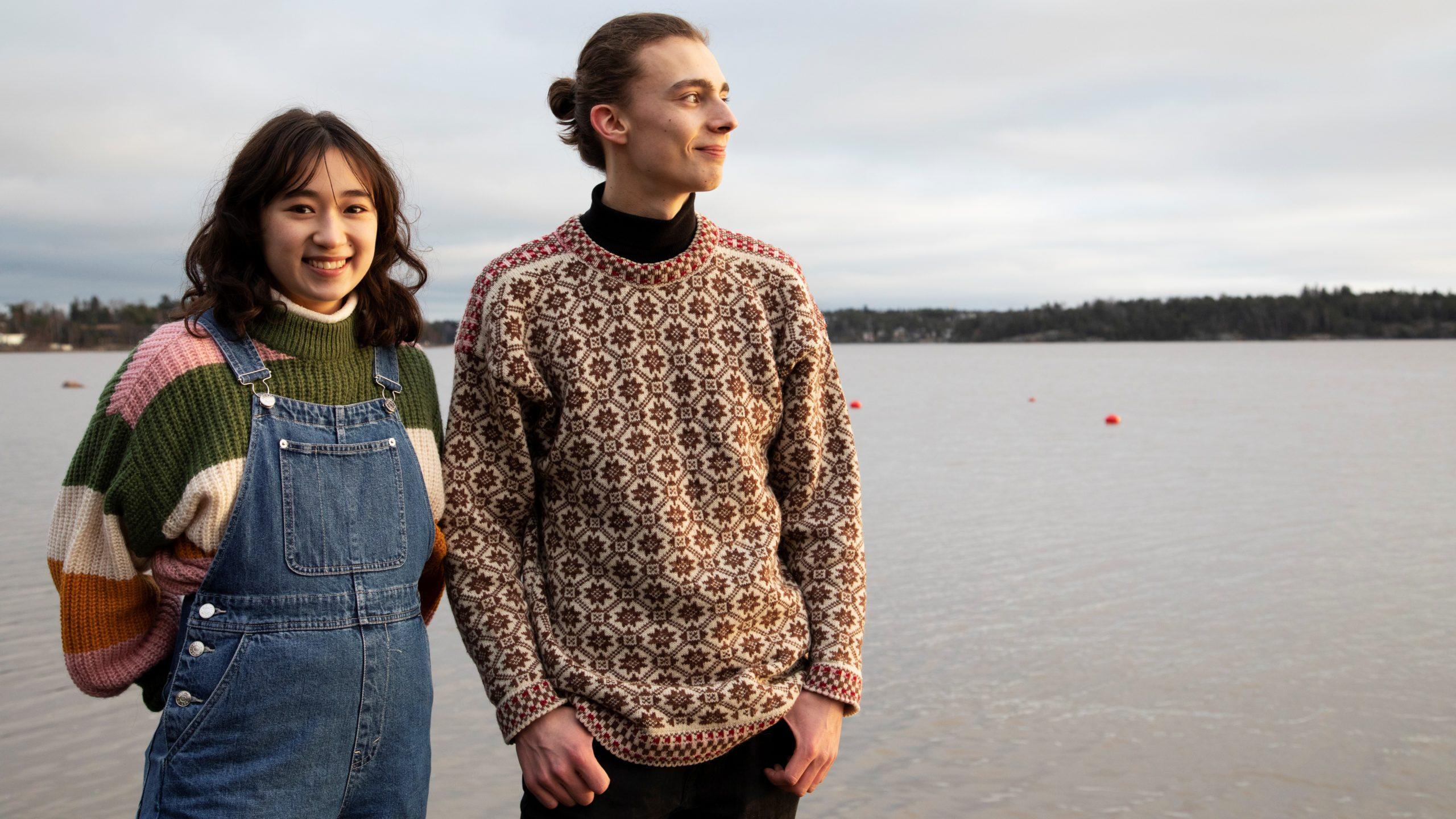 Nainen ja mies seisovat vierekkäin hymyillen järven rannalla.