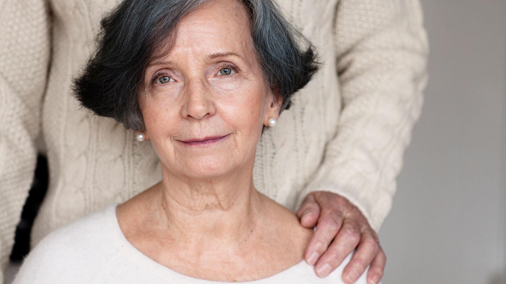 Nainen kasvot kohti kameraa ja takanaan seisoo ihminen, jonka käsi on hänen olkapäällään.
